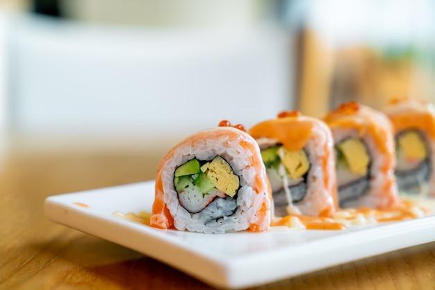Sushi roll di salmone con salsa in cima - stile di cibo giapponese