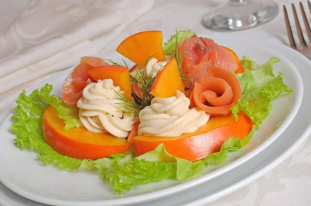 Insalata di salmone con cachi e crema di formaggio closeup