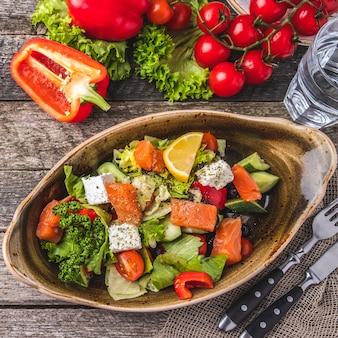 Insalata di salmone con peperoncino, pomodorini, insalata, formaggio, cetriolo e olive nere. concetto per un pasto gustoso e sano. vista dall'alto. avvicinamento