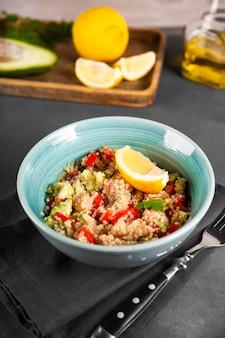 Insalata di salmone con pomodori, avocado e quinoa in una ciotola blu su una foto verticale da tavolo grigio scuro, un piatto di dieta equilibrata.