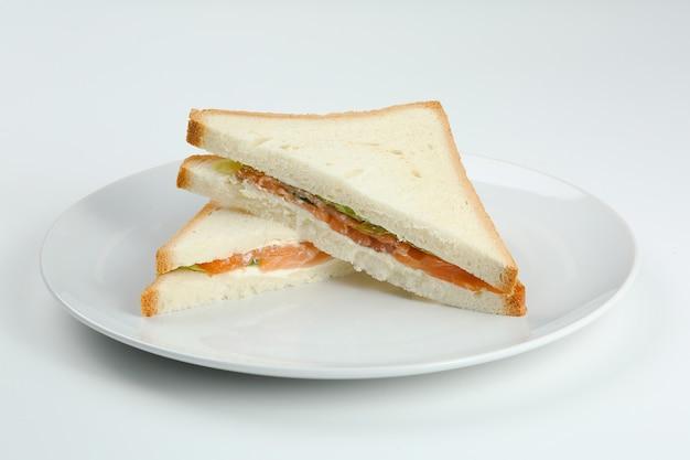 Panino al salmone con pane tostato su piastra bianca. club sandwich al salmone