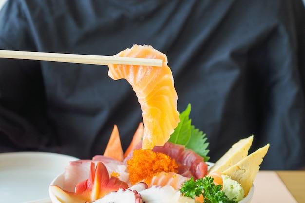 Fetta di salmone in bacchette, mangiare cibo giapponese sashimi rice bowl chirashi don