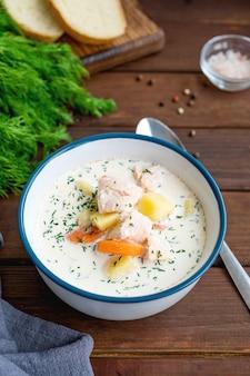 Zuppa di salmone con crema di patate carote ed erbe in una ciotola su fondo scuro zuppa di lohikeitto