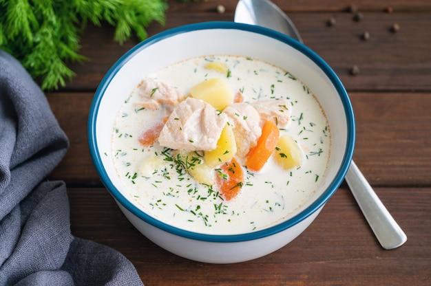 Zuppa di salmone con panna, patate, carote ed erbe aromatiche in una ciotola. zuppa di lohikeitto.