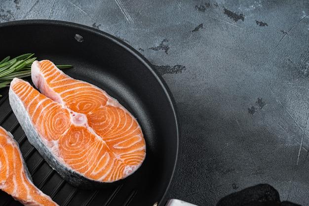 Pesce crudo di bistecca di color salmone sulla padella alla griglia, sul tavolo grigio.