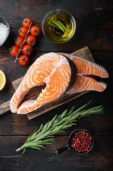 Trancio di salmone pesce crudo con erbe aromatiche, su un vecchio tavolo di legno