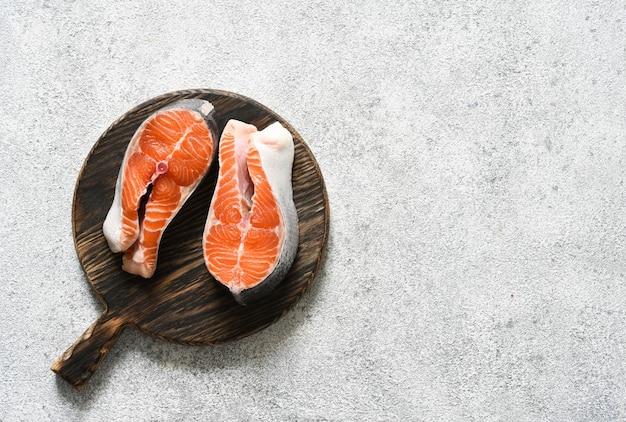 Pesce crudo di bistecca di salmone con spezie preparato per la cottura su una tavola di legno rotonda su uno sfondo di cemento chiaro.