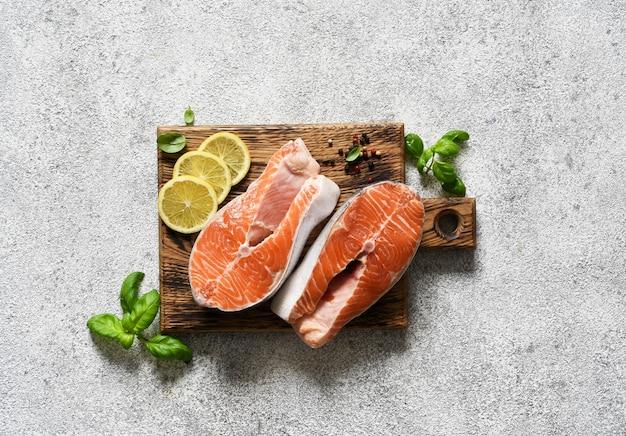 Pesce crudo di bistecca di color salmone con spezie preparato per la cottura. vista dall'alto su sfondo chiaro e concreto.