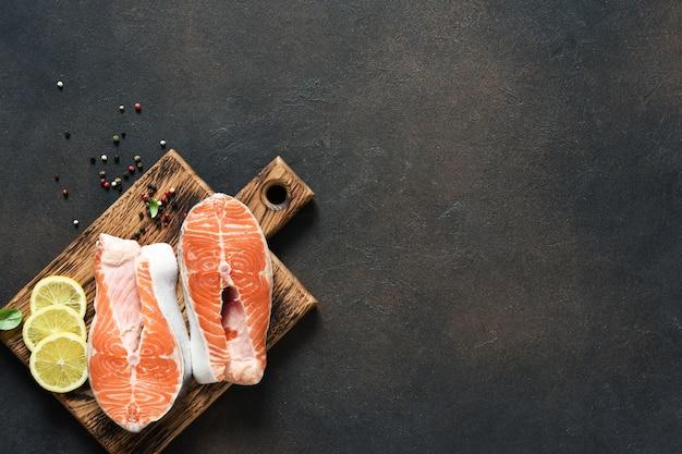 Bistecca di salmone pesce crudo con spezie preparato per la cottura su una tavola di legno su uno sfondo di cemento scuro.