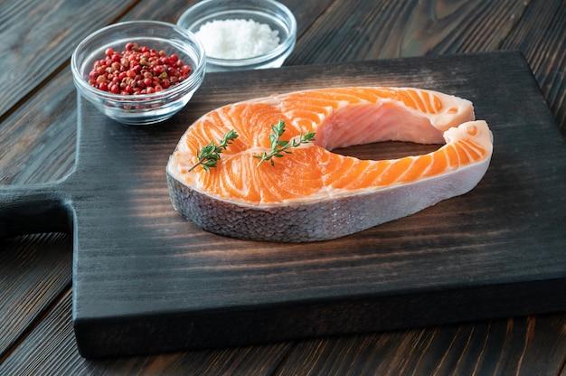 Trancio di salmone con timo fresco e condimenti sulla tavola di legno