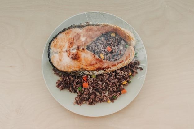 Trancio di salmone con riso fritto sul piatto e sigillato con plastica