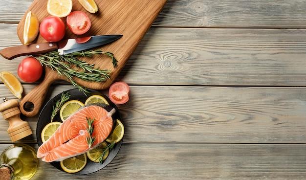 Trancio di salmone con ingredienti per cucinare su un tavolo in legno con copia spazio.