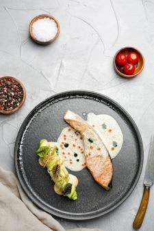 Bistecca di salmone con salsa sul piatto in ceramica. salmone al forno con involtino di zucchine e ingredienti su tavola di cemento