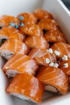 Primo piano dei sushi di color salmone in una scatola