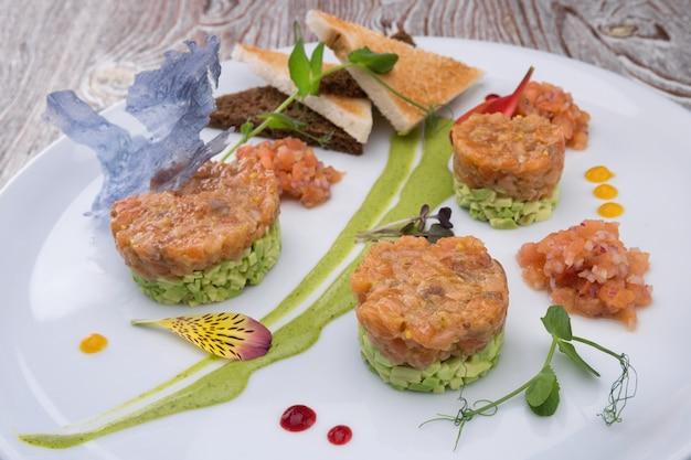 Tartare di salmone con avocado su un piatto bianco