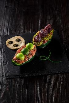 Tartare di salmone e insalata di avocado su sfondo nero. la presentazione originale dei piatti dello chef