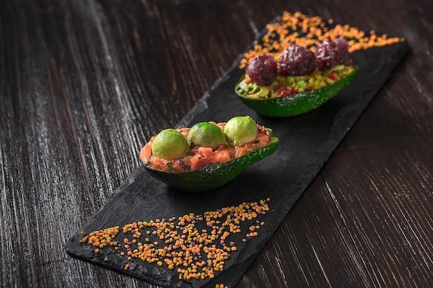 Tartare di salmone e insalata di avocado su fondo nero