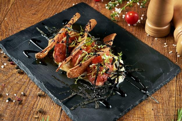 Tartare di salmone su crostini fritti servita su un elegante piatto nero. alimento del ristorante. bakcground in legno. avvicinamento