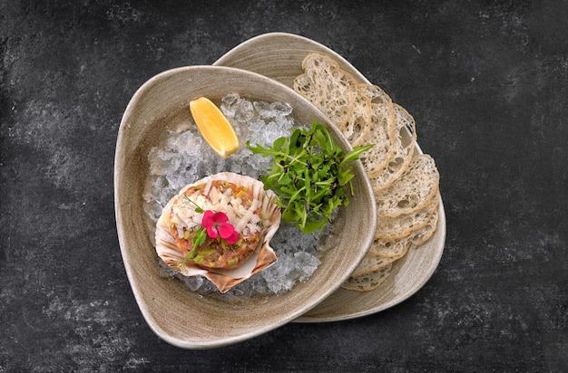 Tartare di salmone con avocado, chips di pane e limone, su un piatto, su uno sfondo scuro, su un ghiaccio ghiacciato