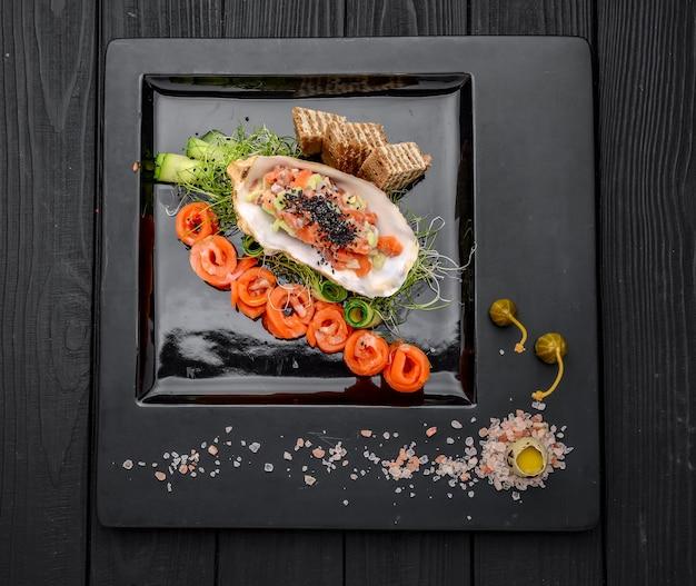 Tartare di salmone con verdure fresche e pane tostato. sul tavolo di legno
