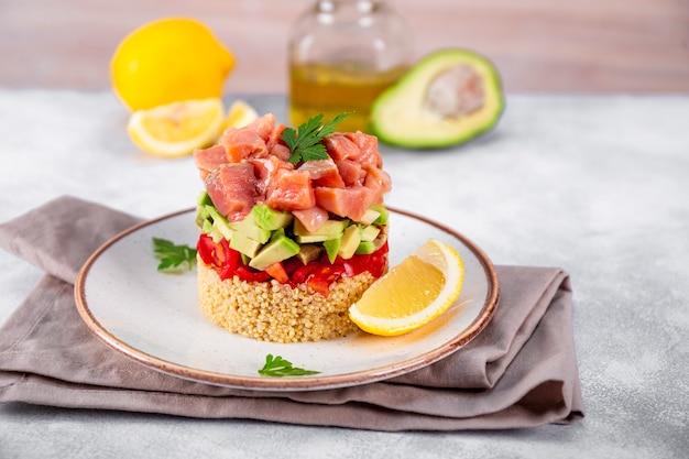Tartare di salmone con pomodori, avocado e quinoa su un piatto e tavolo grigio chiaro.