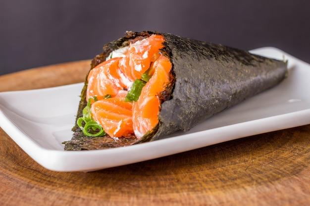 Sushi di temaki di color salmone sulla zolla bianca