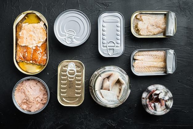 Salmone, tonno, trota sgombro e acciuga - conserve di pesce in barattoli di latta, su fondo nero