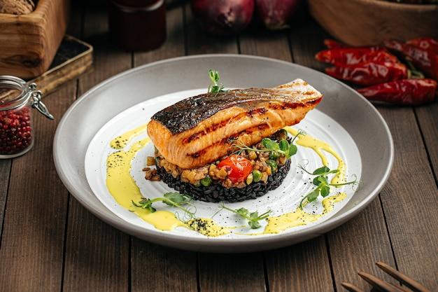 Salmone con salsa cremosa al basilico e riso nero