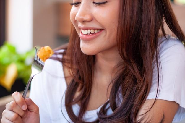 Salmone. una donna con un sorriso luminoso si diverte a mangiare al ristorante.