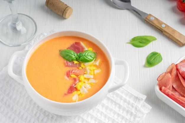 Salmorejo zuppa spagnola di pomodoro frullato con foglia di basilico e uovo sodo con bicchiere di vino