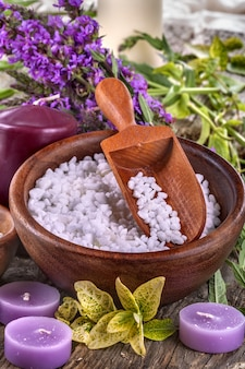 Bagno di sale in una ciotola di legno con fiori e foglie sullo sfondo