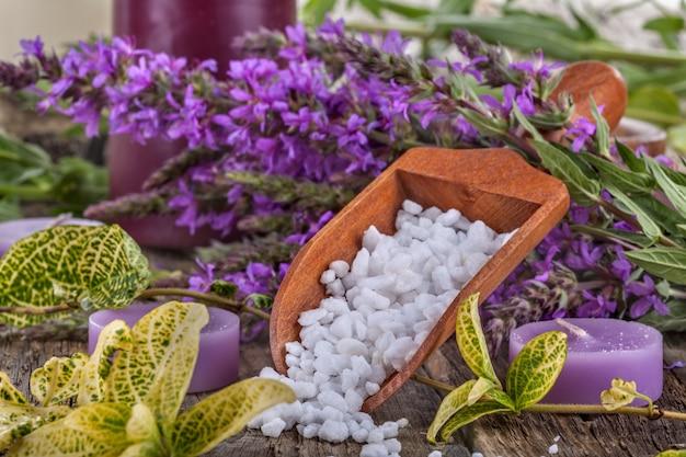 Bagno di sale in cucchiaio di legno con fiori e foglie sullo sfondo