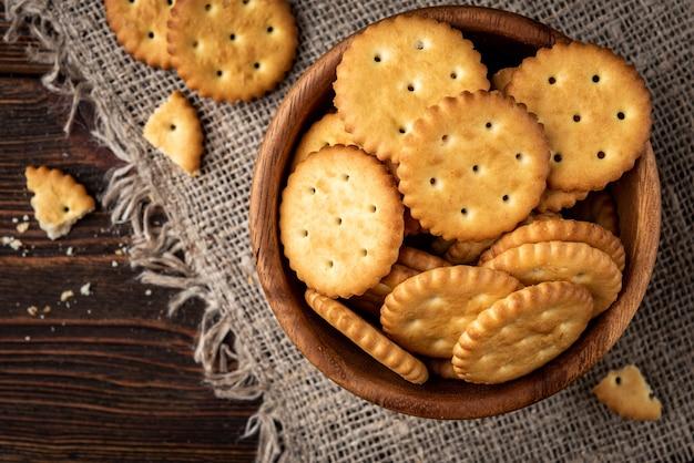 Cracker di sale in ciotola di legno su fondo di legno.