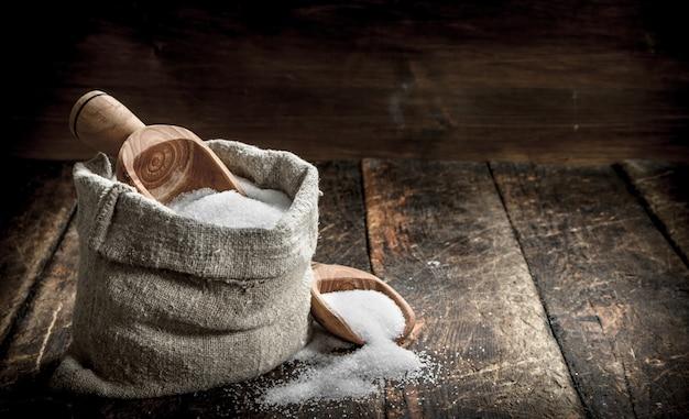 Salare in un cucchiaio di legno. sullo sfondo di legno.