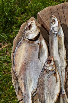 Pesce essiccato all'aria salato che si trova sul ceppo di legno all'aperto