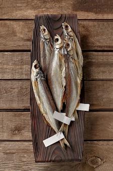 Pesce sciabola salato essiccato all'aria con etichette sulle code su piatto da portata in legno