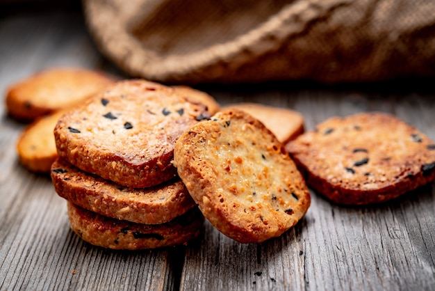 Cracker croccanti salati con sesamo e semi di girasole sul vecchio tavolo da cucina. cibo salutare