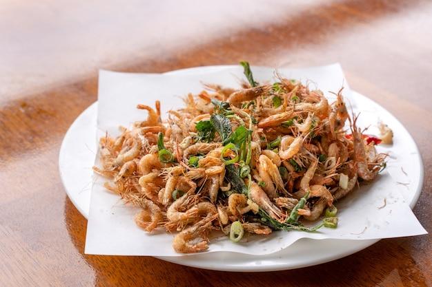 Gamberi croccanti fritti salati gamberetti di fiume macrobrachium nipponese in un piatto bianco sul tavolo di legno delizioso cibo di strada taiwanese lifestyle