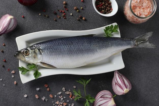 Aringhe salate con cipolla rossa, peperoni, sale marino e prezzemolo su sfondo grigio. vista dall'alto