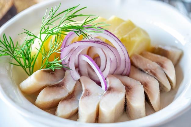 Aringa marinata salata tagliata per fette e fette di patata bollita con anelli di cipolla fresca e aneto sul primo piano piatto bianco.