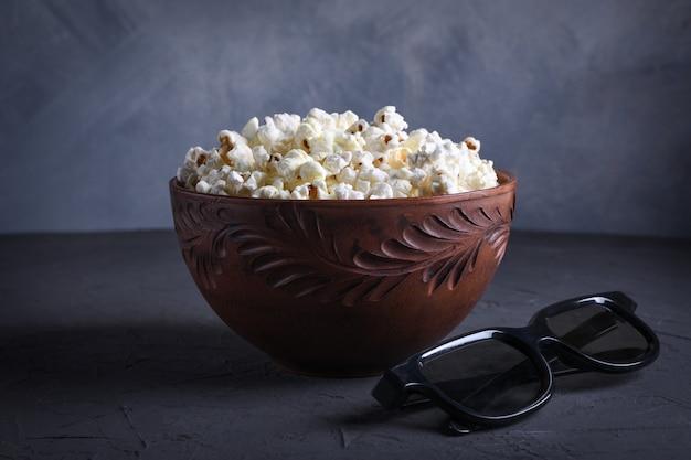 Popcorn salato in una ciotola con occhiali 3d su un tavolo su uno sfondo grigio. vista frontale