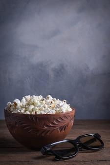Popcorn salato in una ciotola con occhiali 3d su un tavolo di legno su uno sfondo grigio. vista frontale