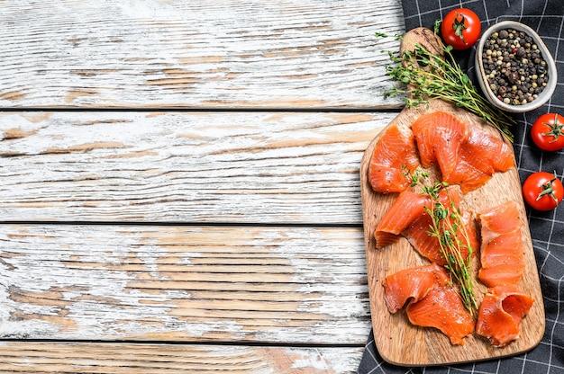 Fette di salmone salato con pepe e timo. pesce biologico. sfondo bianco. vista dall'alto. copia spazio.
