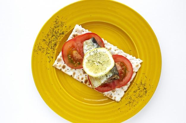 Cracker salati con sardina, pomodoro e limone dall'alto