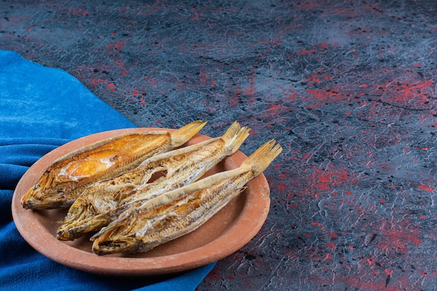 Pesce essiccato salato isolato su un piatto di argilla su uno sfondo scuro.