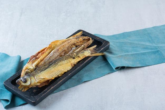 Pesce essiccato salato isolato su una tavola di legno