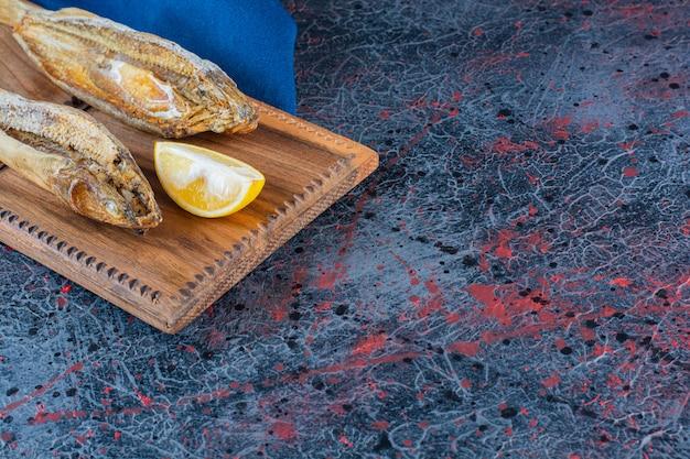 Pesce essiccato salato con una fetta di limone isolato su una tavola di legno