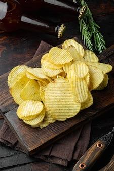 Set snack salato con patatine fritte, su un vecchio tavolo di legno scuro