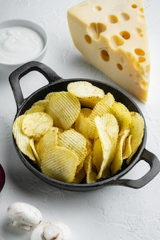 Set snack salato con patatine fritte con formaggio e cipolla, con salse per immersione salsa di pomodoro panna acida, su superficie di pietra bianca