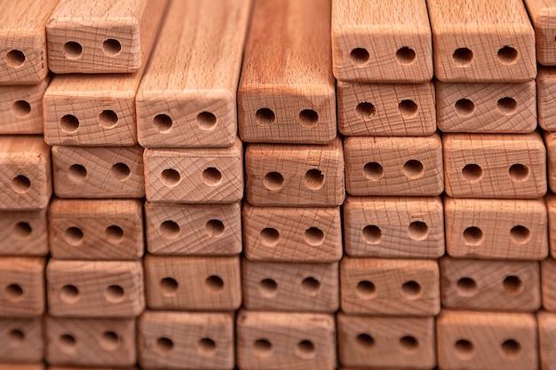 Stesse barre di legno con fori praticati per la produzione di mobili giacciono in file